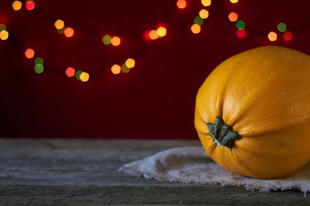 Jesieni tło na ciemnej drewnianej powierzchni, żółta bania na tle rozmyci światła