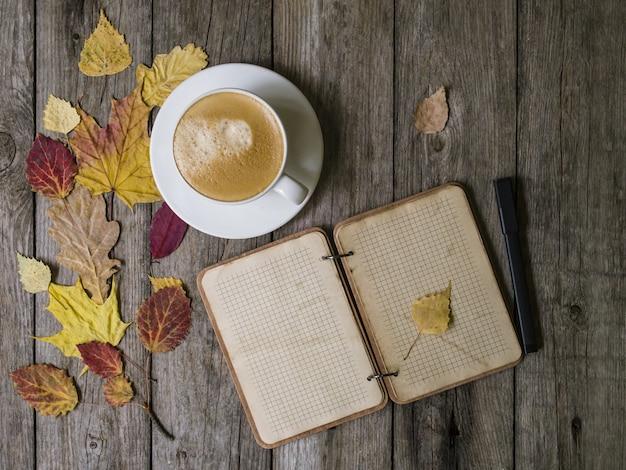 Jesieni tło na drewnianym stole z jesieni suchymi barwionymi liśćmi