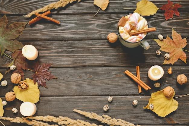Jesieni tło robić wysuszeni spadków liście, kubek kakao z marshmallows, dokrętkami, cynamonem, szkocką kratą, jabłkami. widok z góry na brązowe drewno