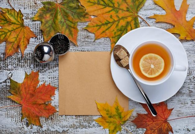 Jesieni tło z liśćmi, banią i filiżanką herbata