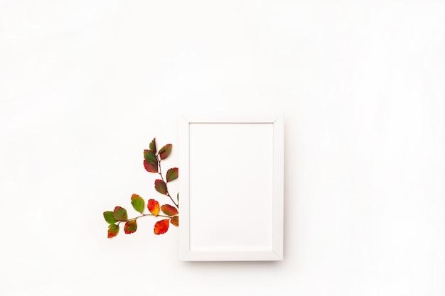 Jesieni tło z naturalnym wystrojem. biała ramka na zdjęcia, jesienne liście suszone. leżał płasko, widok z góry. skopiuj miejsce na sezonowe promocje i rabaty