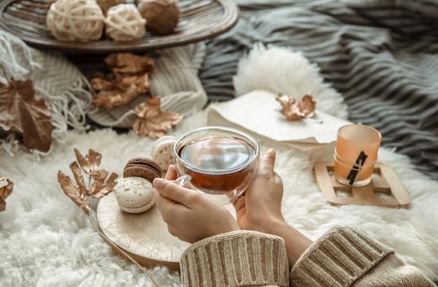Jesieni wciąż życia dziewczyna trzyma filiżankę herbata.