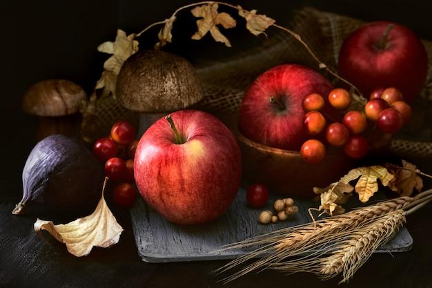 Jesieni wciąż życie w niskim kluczu z różowymi jabłkami i spadek dekoracjami na ciemnym tle