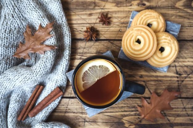 Jesieni wciąż życie z filiżanką herbata, ciastka, pulower i liście na drewnianej powierzchni.