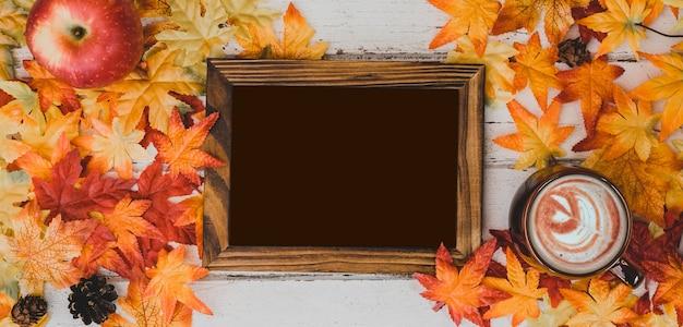 Jesienią i jesienią. gorąca czekolada z ramką na zdjęcia i fałszywym liściem klonu na drewnianym stole. koncepcja róg obfitości zbiorów i święto dziękczynienia.