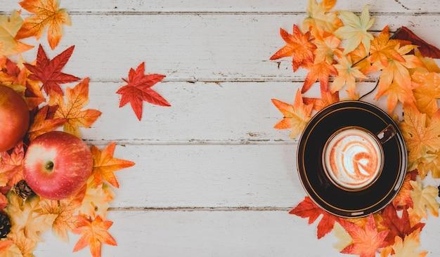 Jesienią i jesienią. gorąca kawa z fałszywym liściem klonu na stole z drewna. koncepcja róg obfitości zbiorów i święto dziękczynienia.