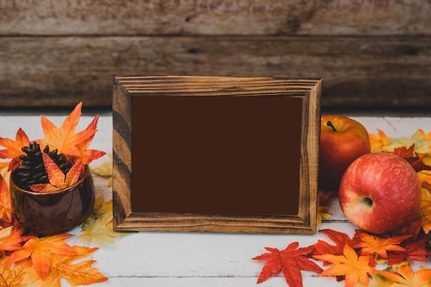 Jesienią i jesienią. pusta ramka na zdjęcia i fałszywy liść klonu na stół z drewna. koncepcja róg obfitości zbiorów i święto dziękczynienia.