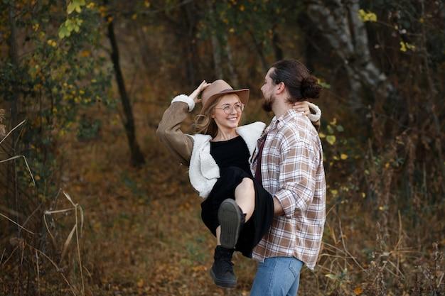 Jesienią mężczyzna trzyma dziewczynę w ramionach