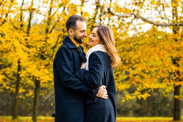 Jesienią para w płaszczach przytula się na zewnątrz