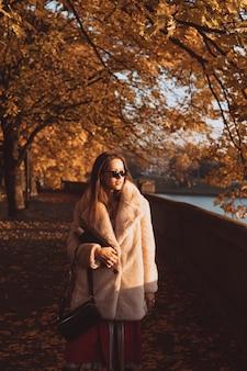 Jesienna aleja z drzewami i żółtymi opadłymi liśćmi.