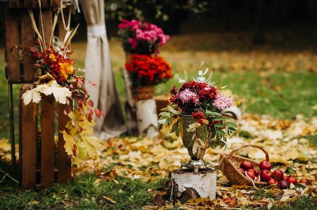 Jesienna ceremonia ślubna na ulicy na zielonym trawniku. udekoruj łukami świeżych kwiatów na uroczystość.