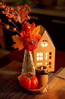 Jesienna dekoracja kuchni - świecący domek z tektury, świeca, bukiet z jesiennych liści, persimmon