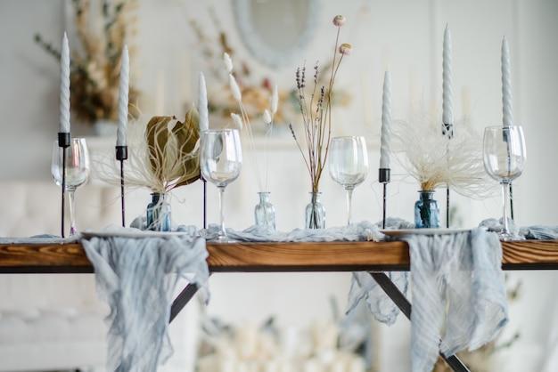 Jesienna dekoracja stołu, drewniany stół podany z suszonym kwiatkiem, biały talerz, zabytkowe sztućce, świeczki z jasnoniebieskim obrusem z gazy. widok z góry, selektywne focus.