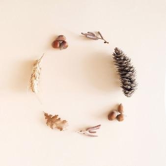 Jesienna dekoracja ułożona w okrąg. szyszka, orzech laskowy, liść, ziarno na kremowym tle. pastelowy przyjemny upadek koncepcja z miejsca na kopię.