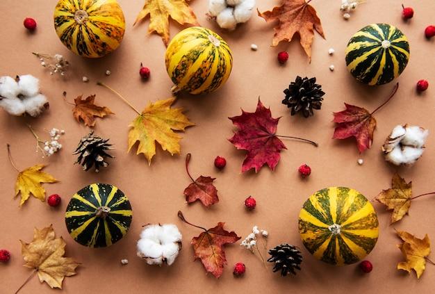 Jesienna dekoracja z dyni i suchych liści klonu na brązowym tle