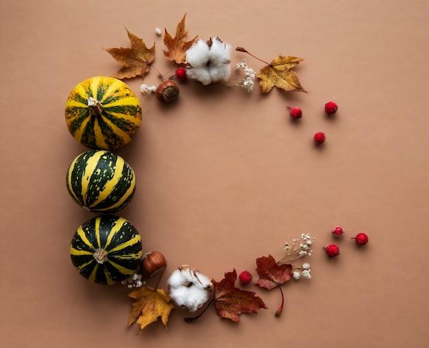 Jesienna dekoracja z dyni i suchymi liśćmi klonu w kształcie koła na brązowym tle
