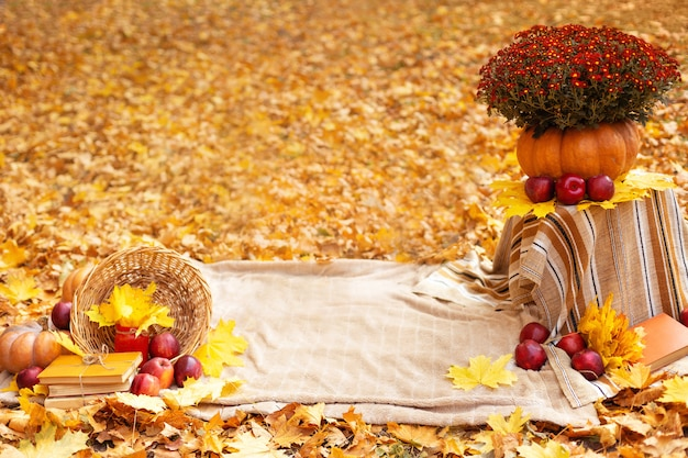 Jesienna dekoracja z kwiatami, liśćmi klonu, czerwonymi jabłkami, dynią, kocem i starymi książkami