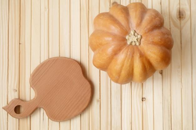 Jesienna dynia na drewnianym stole na desce
