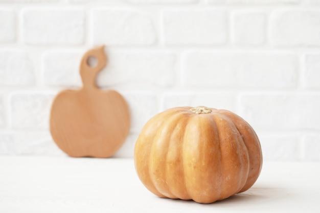 Jesienna dynia z drewnianą deską do krojenia na białej ścianie z cegieł