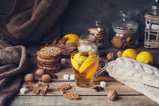 Jesienna gorąca herbata z cytryną i przyprawami w szklanym kubku. zdrowa herbata z ciasteczkami, orzechami włoskimi i liśćmi dookoła. koncepcja upadku