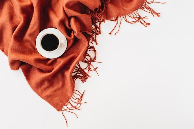 Jesienna, jesienna kompozycja. filiżanka kawy leżąca na ciepłym, imbirowym kocu