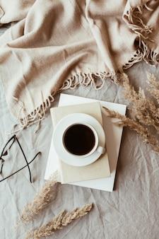 Jesienna, jesienna kompozycja. filiżanka kawy leżąca na szarym lnianym łóżku z beżowym ciepłym kocem, książkami, szklankami i trzciną