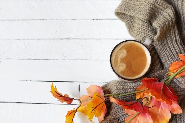 Jesienna kawa nad białym drewnem