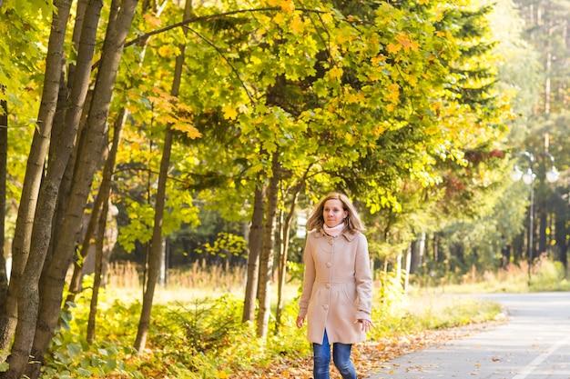 Jesienna kobieta i jesień żółty klonowy ogród w tle