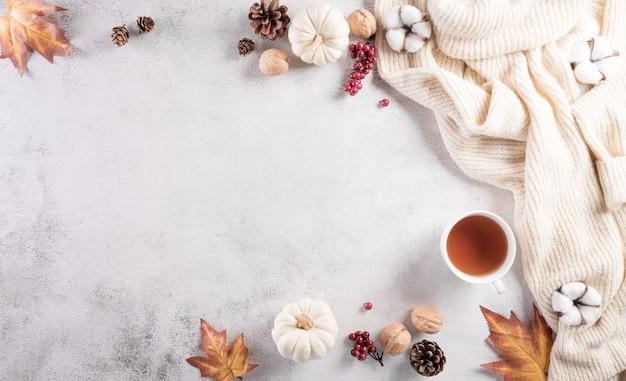Jesienna kompozycja bawełna dyniowa kwiaty jesienne liście i sweter na kamieniu