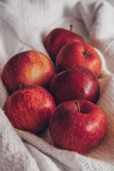 Jesienna kompozycja. czerwone jabłka w białych swetrach z dzianiny. cicha przytulna domowa scena. zbiór, uprawa, żniwa. koncepcja jesień