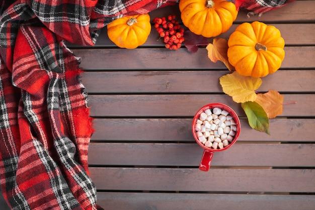Jesienna kompozycja, czerwony kubek z kakao i piankami.