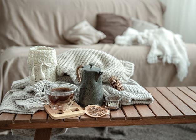 Jesienna kompozycja domowa z filiżanką herbaty, czajniczkiem i dzianinowym elementem.