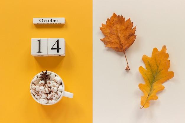 Jesienna kompozycja. drewniany kalendarz 14 października, kubek kakao z piankami i żółtymi jesiennymi liśćmi.