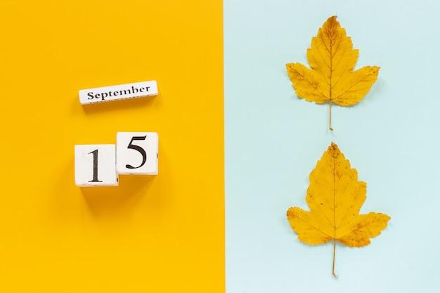Jesienna kompozycja. drewniany kalendarz 15 września i żółte jesienne liście na żółtym niebieskim tle.