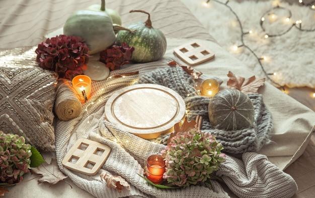 Jesienna kompozycja dyni, kwiatów hortensji, detali wystroju domu ze świecami i gerlandem.