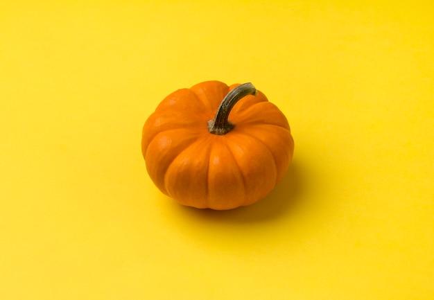 Jesienna kompozycja. dynia na żółtym stole. widok z góry