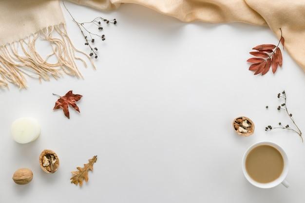Jesienna kompozycja. filiżanka kawy, kratka, świeca, suszone liście na białym tle