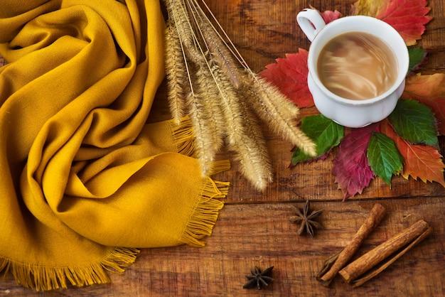 Jesienna kompozycja filiżanki herbaty, żółty szalik, liście i kłoski, laski cynamonu na drewnianym tle. miejsce na tekst, skopiuj miejsce. jesienne tło. ciepła, przytulna atmosfera jesieni. układ płaski, układ