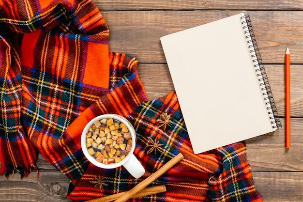 Jesienna kompozycja flatlay. czerwony szalik damski, vintage papierowy notatnik, filiżanka herbaty, długopis, laska cynamonu