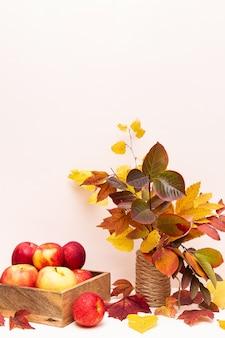 Jesienna kompozycja jabłek i kolorowych opadłych liści. koncepcja zbioru