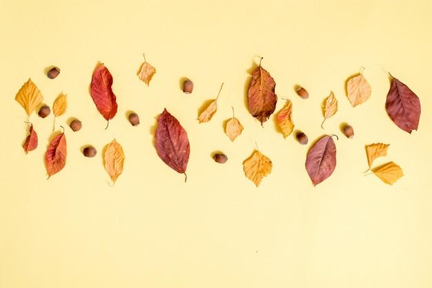 Jesienna kompozycja, jesienne liście, gorąca parująca filiżanka herbaty i ciepły szalik na drewnianym stole tle.