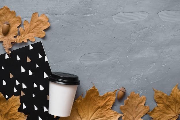 Jesienna kompozycja. kawa na wynos, notatnik, słuchawki z jesiennych liści. leżał płasko, widok z góry, miejsce.