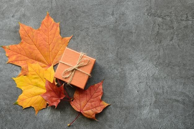 Jesienna kompozycja. liście klonu i pudełko. leżał płasko, widok z góry