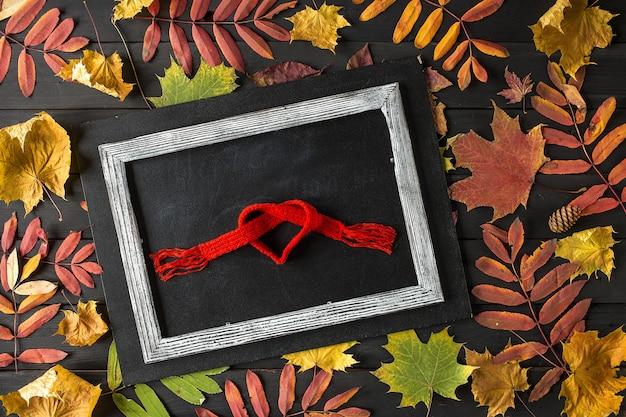 Jesienna kompozycja martwa natura kreatywna. rama wykonana z jesiennych liści i szalika.