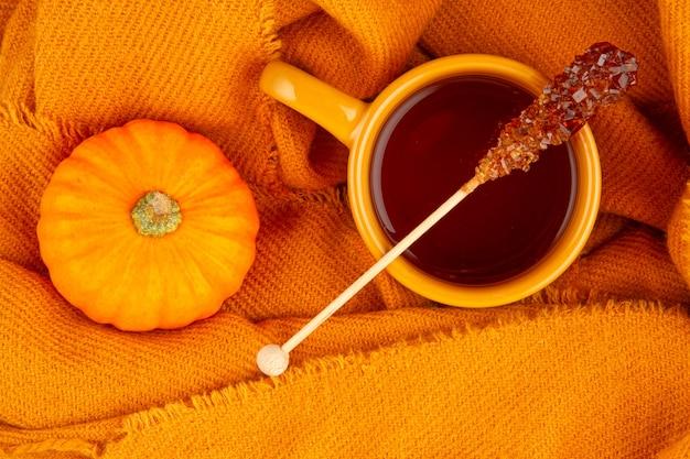 Jesienna kompozycja na płasko leżąca z herbatą i ciepłym wełnianym szalikiem