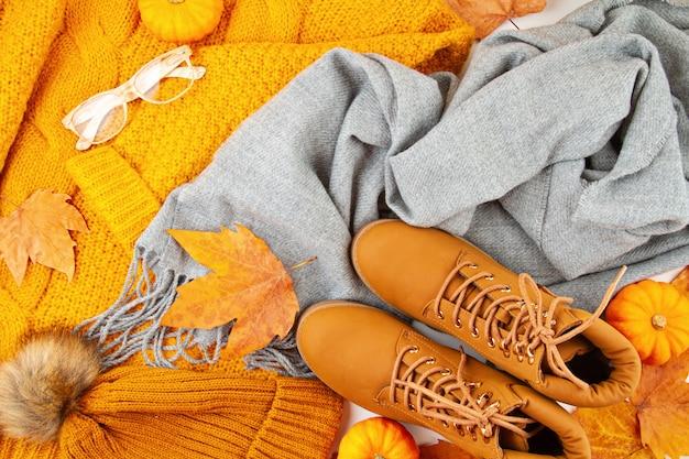 Jesienna kompozycja na płasko, z jesiennymi liśćmi, dyniami, butami oraz ciepłym wełnianym szalikiem i swetrem