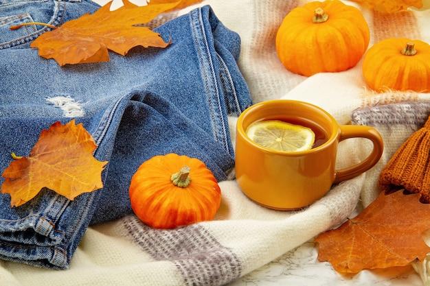 Jesienna kompozycja na płasko, z jesiennymi liśćmi, filiżanką gorącej herbaty, dżinsami i ciepłym wełnianym szalikiem i czapką