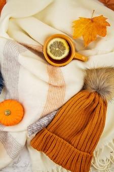 Jesienna kompozycja na płasko, z opadającymi liśćmi, filiżanką gorącej herbaty, szalikiem i ciepłym wełnianym pomarańczowym kapeluszem