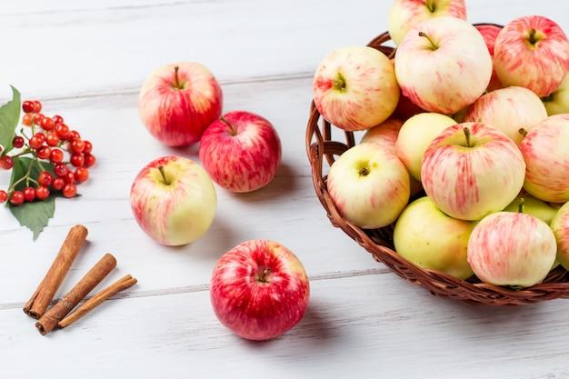 Jesienna kompozycja nastrojowa z czerwonymi jabłkami w wiklinowym koszu i żółtych liściach