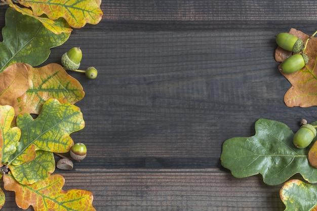 Jesienna kompozycja. obramowanie ramki kolorowe jesienne liście na ciemnym tle drewniane. widok z góry, lato.